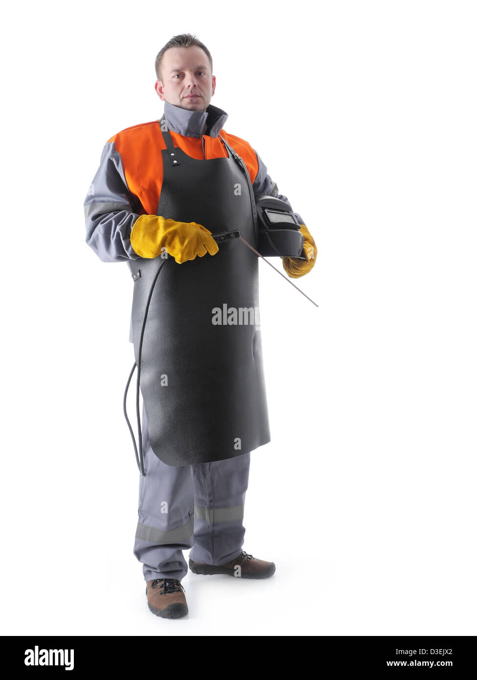 Portrait of welder wearing protective welding black leather apron, welding hood and welding electrode holder over - Stock Image