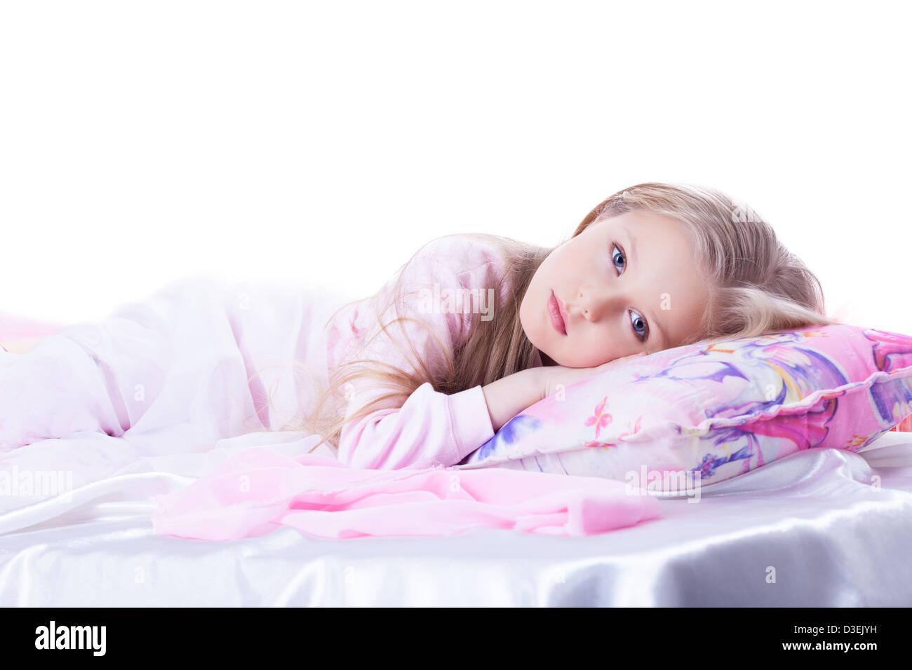 Little girl lying on bed - Stock Image