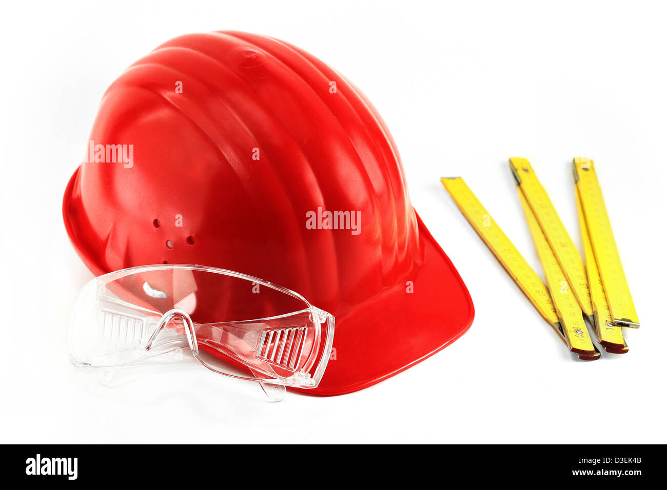 Red protection helmet and transparent protection glasses next to yellow meter - Stock Image