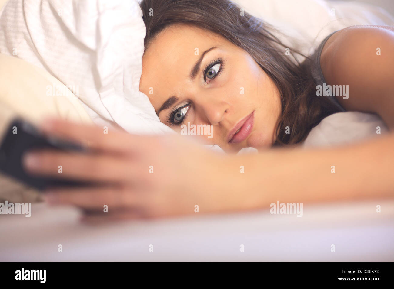Woman lying on bed reading text message from her smartphone - Stock Image