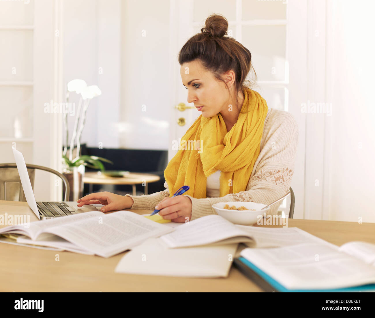 Young university student using laptop and books in studying at home - Stock Image
