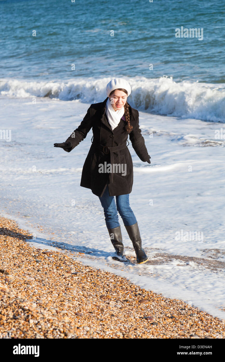 206a5acf71 Girl wearing winter clothes and wellington boots playing in the surf on the  beach. -