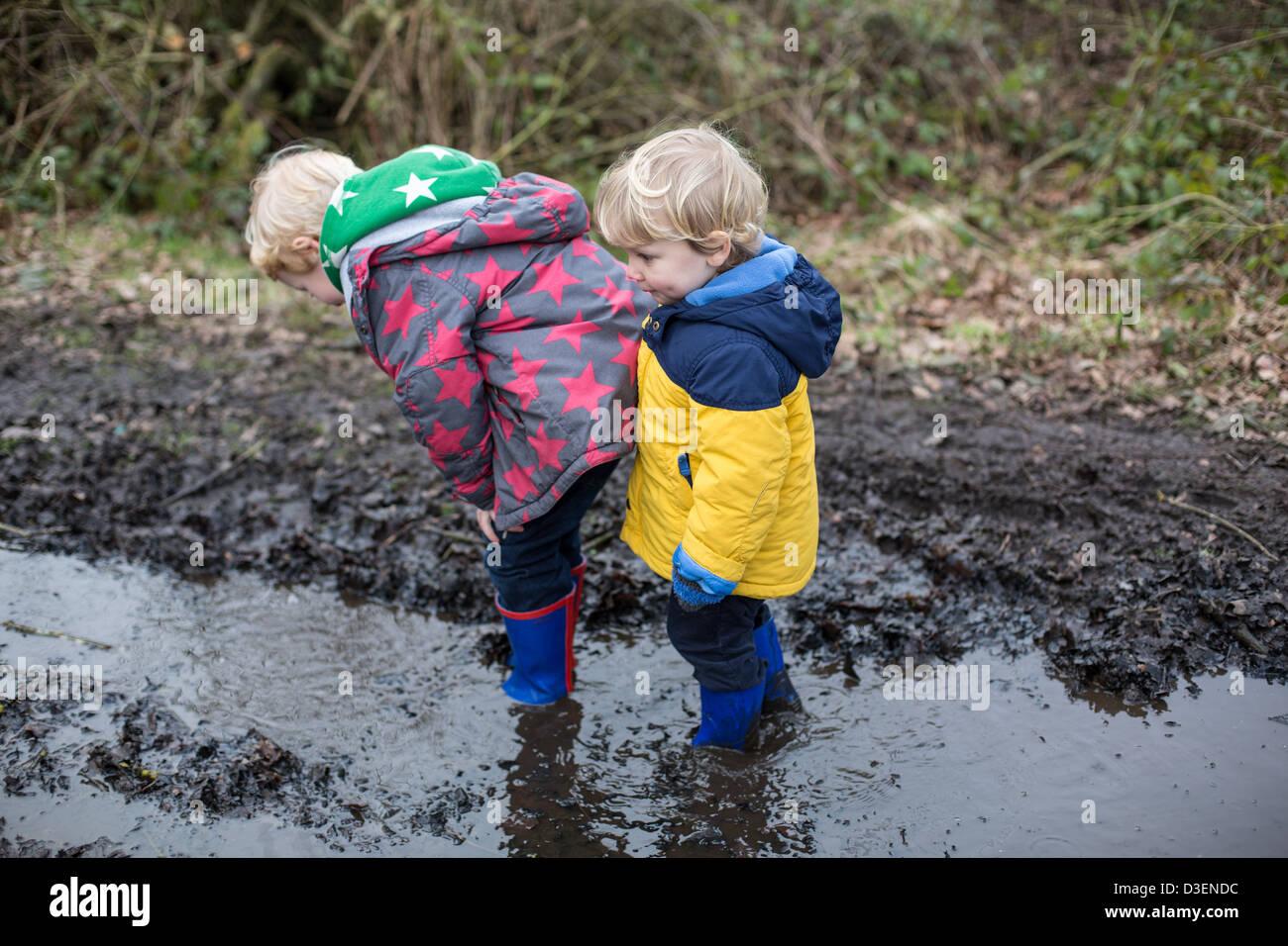 Children walking through Muddy Puddles - Stock Image