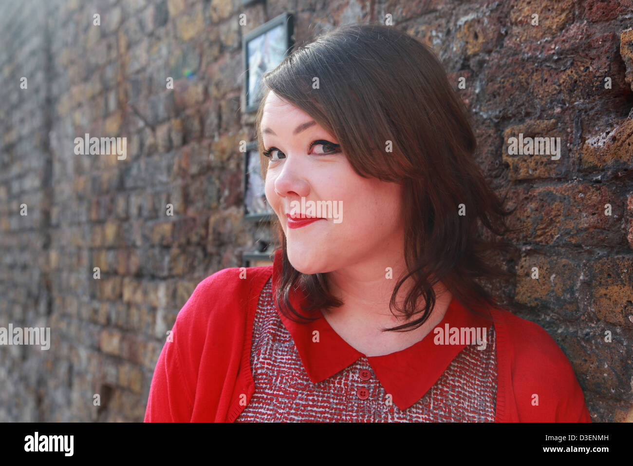 Female in front of colourful wall,Brick Lane, East London E1 Stock Photo