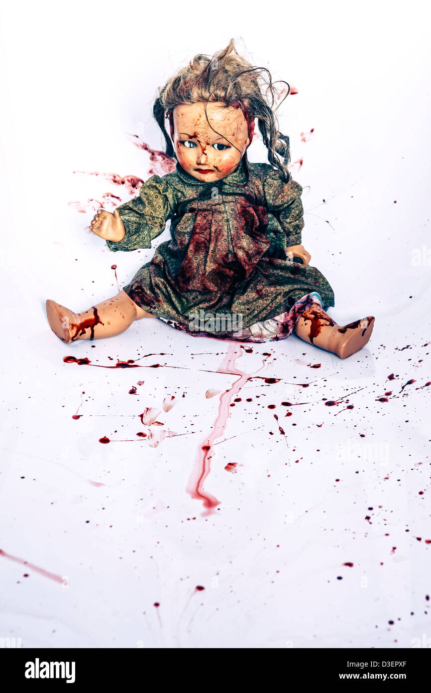 an old, bloody doll in a bath tub - Stock Image
