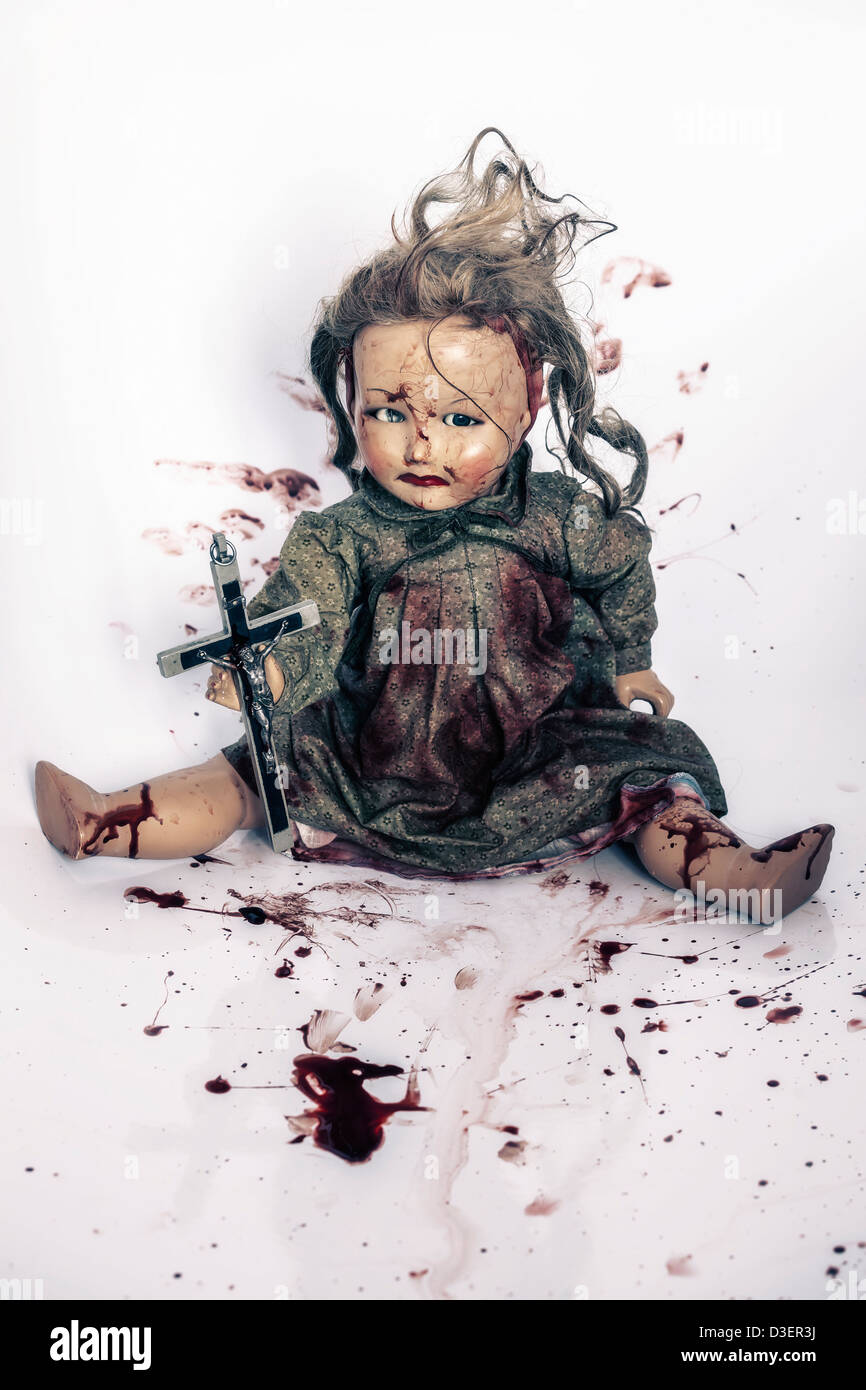 a bloody doll with a crucifix - Stock Image