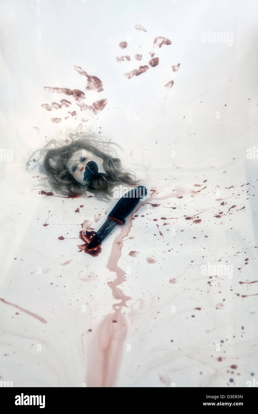 broken head of a doll in a bloody bath tub with a knife - Stock Image