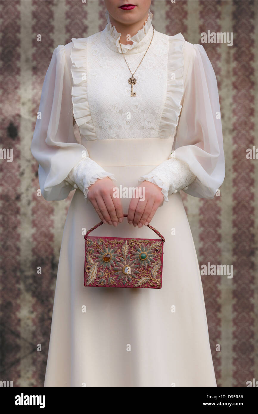 a woman in a victorian dress with a red, beaded handbag - Stock Image