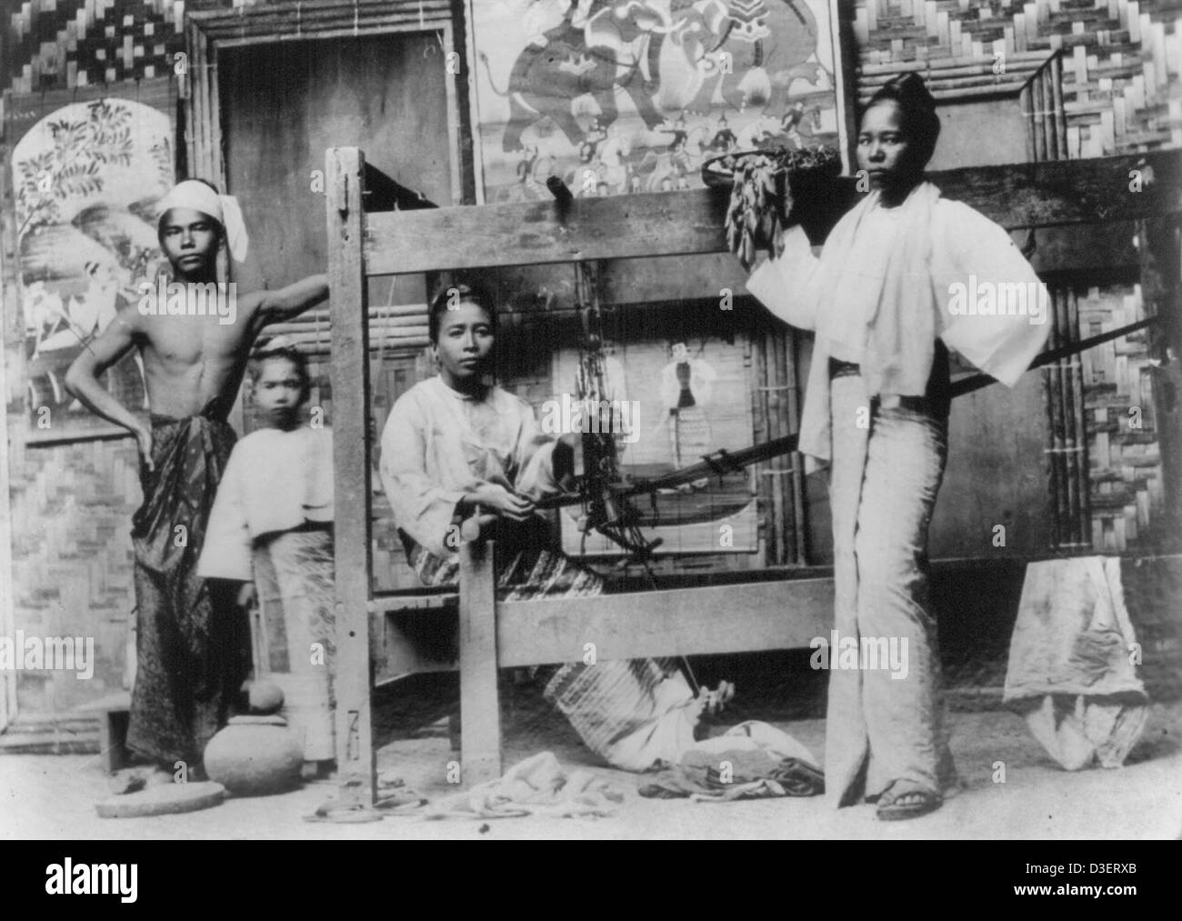 Interior of a Burmese house set up for weaving; a group portrait of a woman sitting at a loom, a woman standing - Stock Image