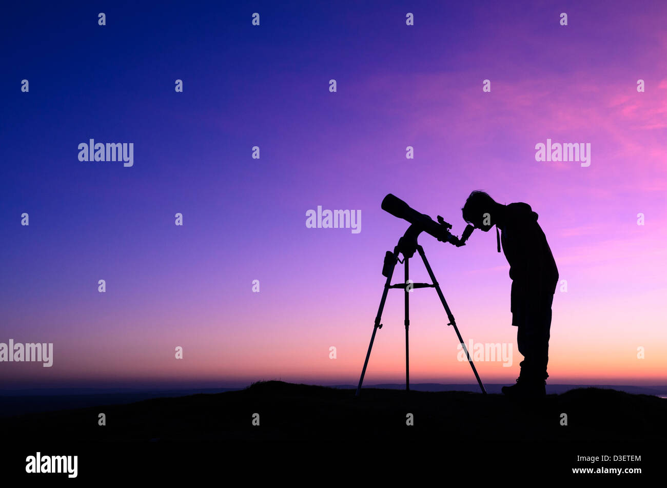 The silhouette of a teenage boy stargazing with a telescope at dusk - Stock Image