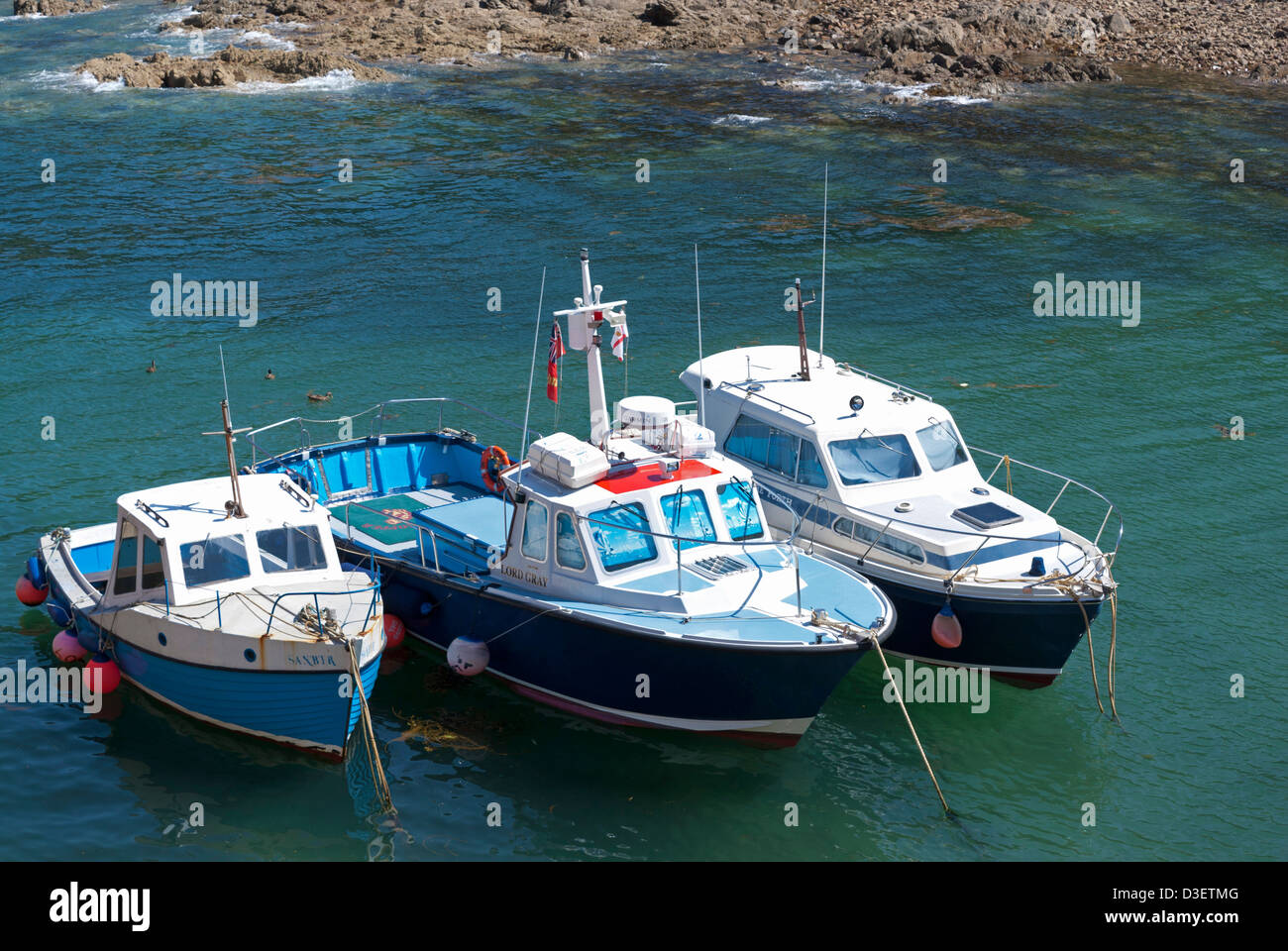 Three small fishing boats in the harbour at Bonne Nuit bay, Jersey, Channel Islands, UK - Stock Image