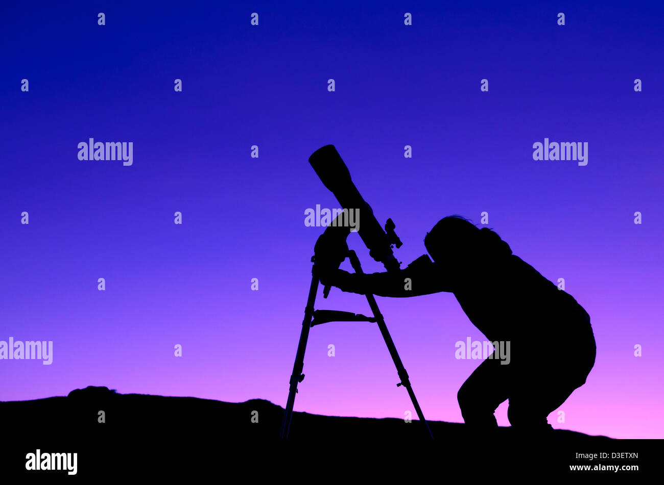 The silhouette of a woman stargazing with a telescope at Dusk - Stock Image