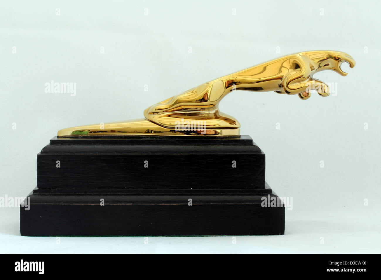 A gold leaping jaguar car bonnet mascot mounted on a plinth. - Stock Image