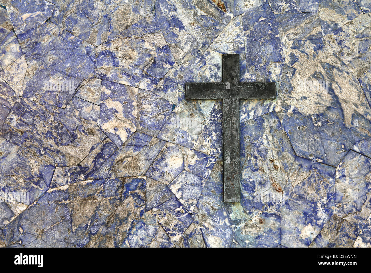 Gravestone texture - blue marble stone and a brass cross. Religious background. - Stock Image