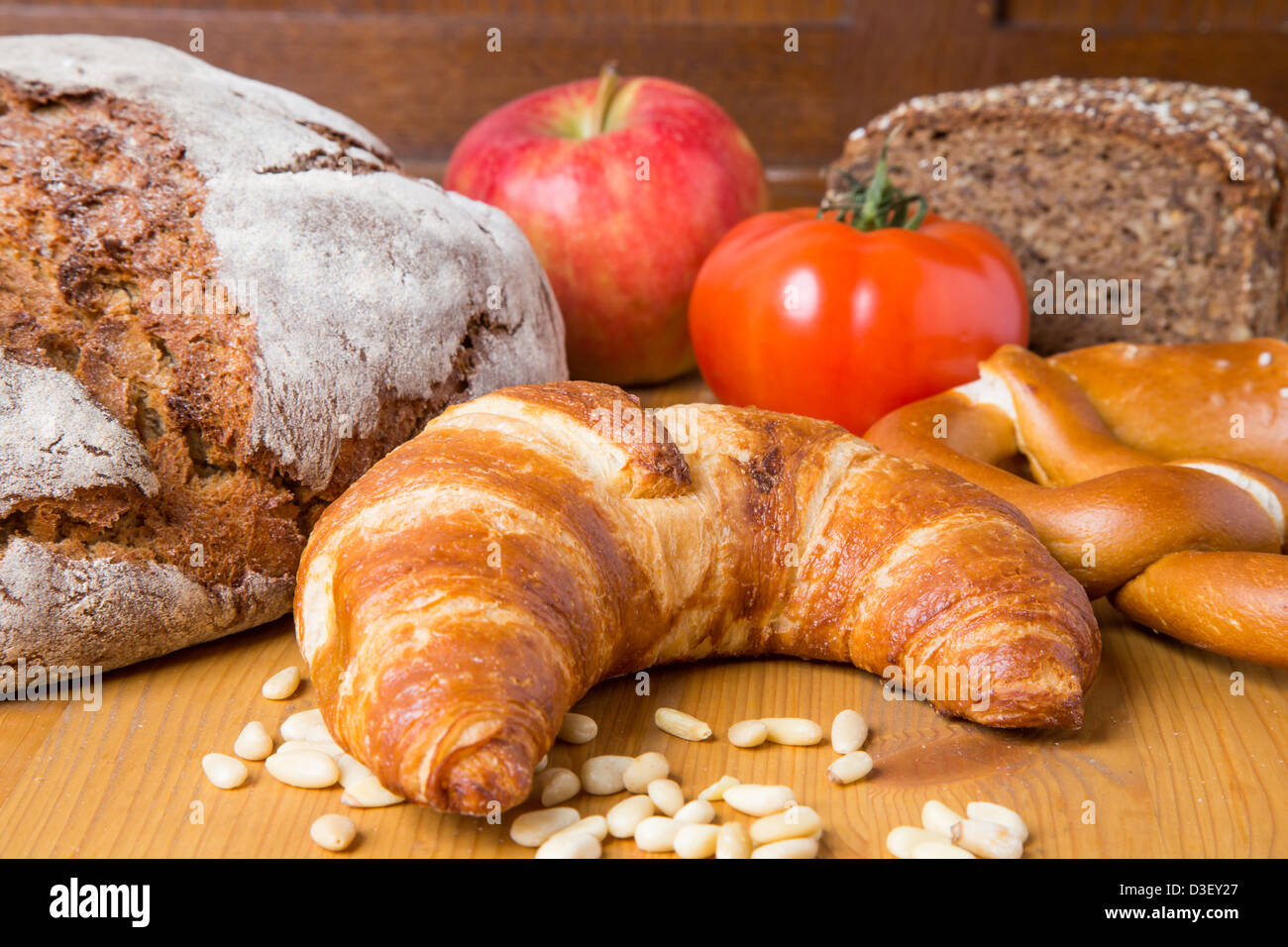 Different types of food such as bread, a tomato, apple, pine seeds and a pretzel Stock Photo