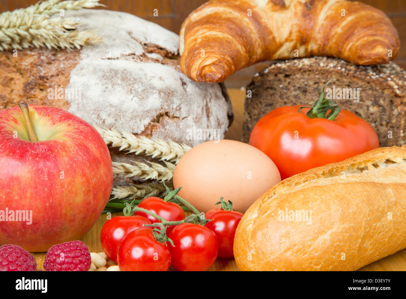 Different types of food such as bread, a tomato, apple, pine seeds, raspberry and a pretzel - Stock Image