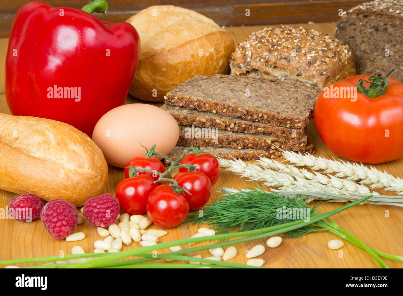Different types of food such as bread, a tomato, apple, pine seeds, raspberry and a pretzel Stock Photo