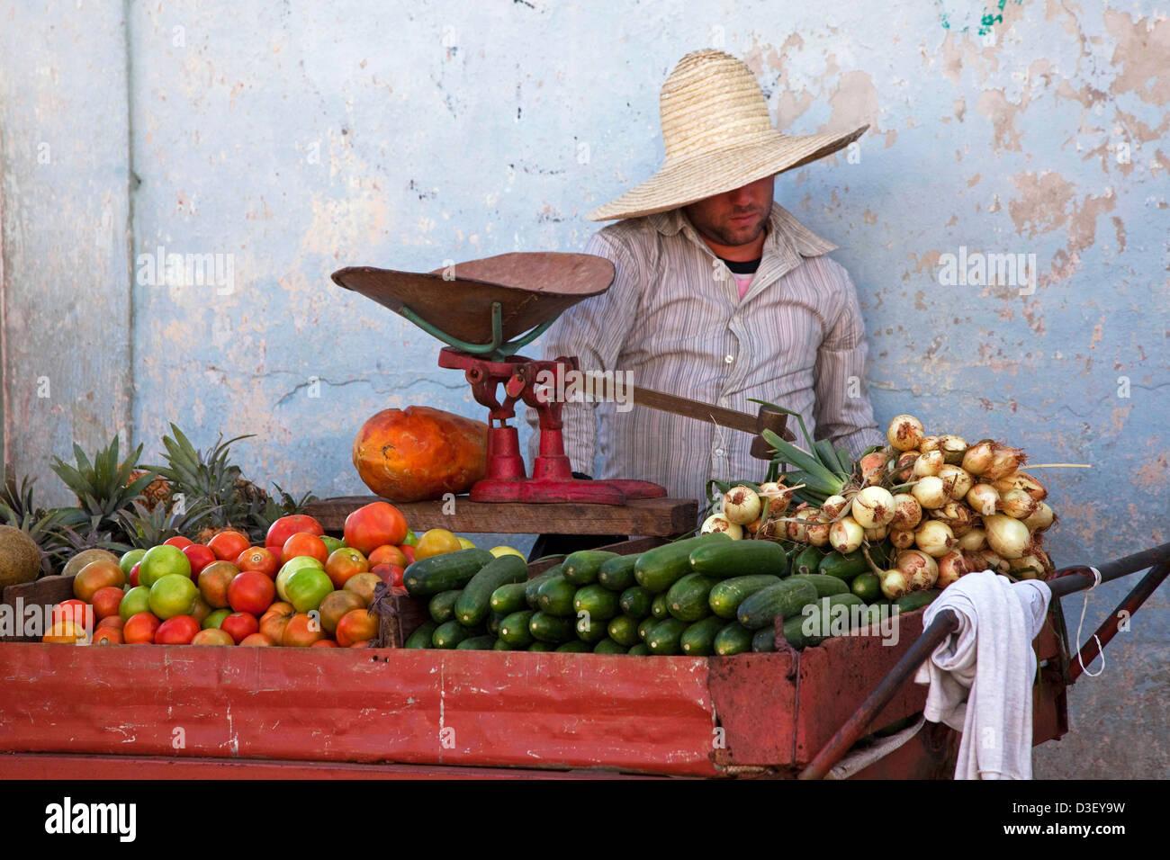 Cuban vendor selling fresh fruit and vegetables at market stall in Viñales, Cuba, Caribbean - Stock Image
