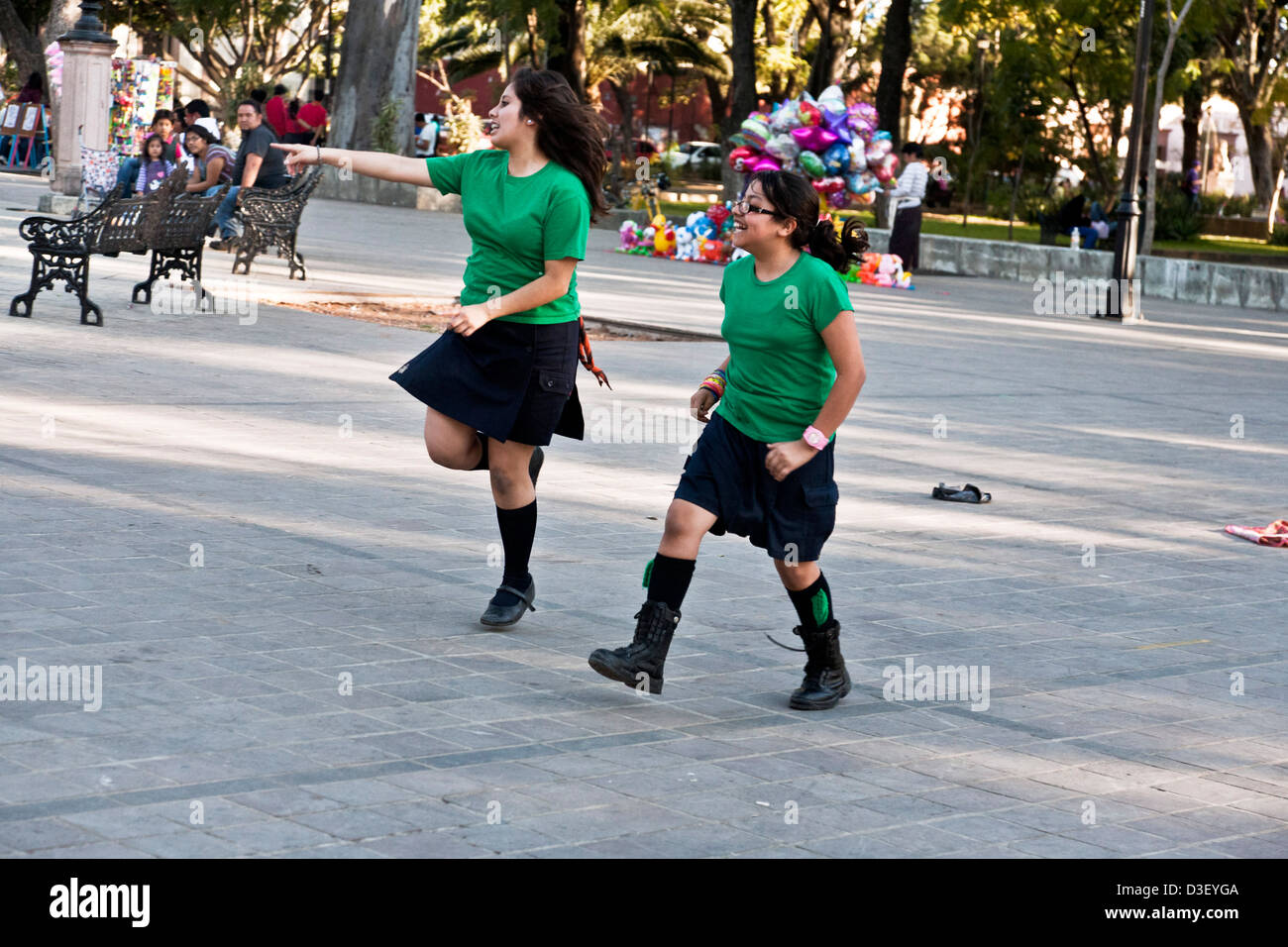 2 pretty tween girl scout scouts laughing as they run in handkerchief relay race as spectators watch Llano park - Stock Image