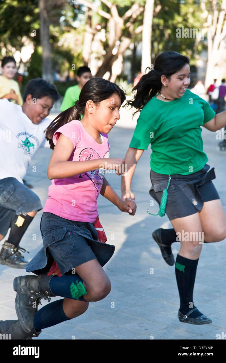 pre teen girl & boy scouts having fun running in one legged handkerchief relay race  Llano park Oaxaca Mexico - Stock Image