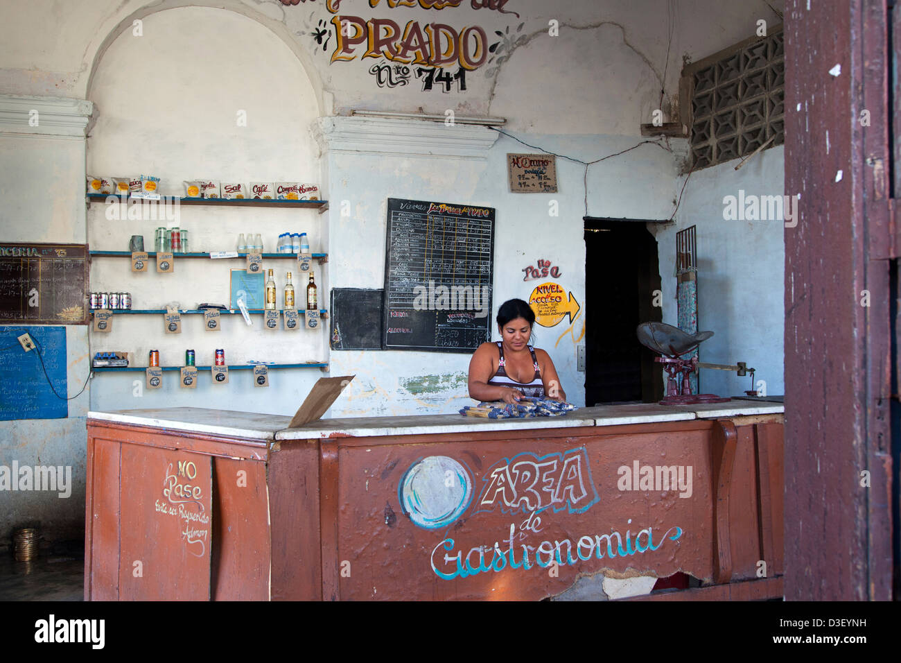 Shopkeeper behind counter of Cuban state shop in Cienfuegos, Cuba, Caribbean - Stock Image