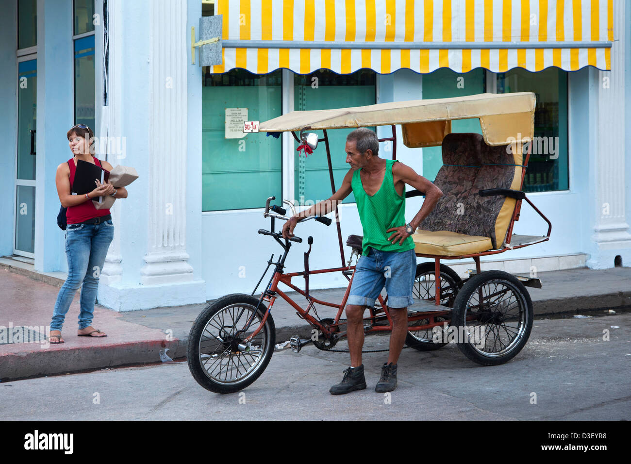Man with three-wheeled bicycle taxi waiting for tourists in Cienfuegos, Cuba, Caribbean - Stock Image
