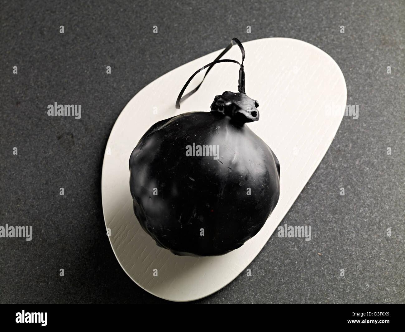 black wax covered cheese 'bomb' - Stock Image