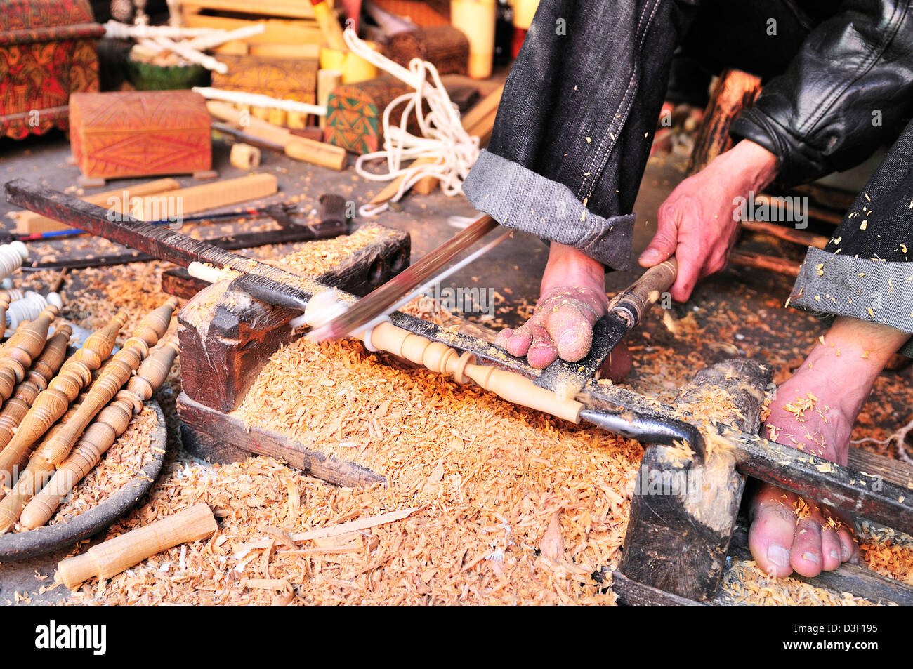 Man in a Medina  souk ,Marrakesh,  uses his feet  to operate his lathe to make decorative spindles for bobins - Stock Image