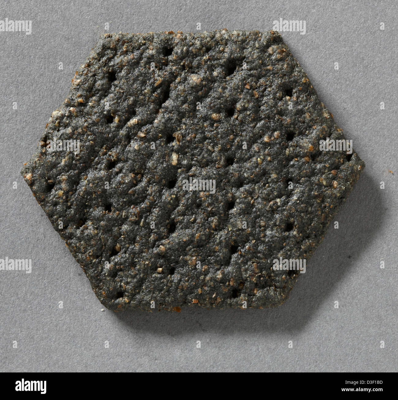 Hexagonal baked savory charcoal biscuit for cheese - Stock Image