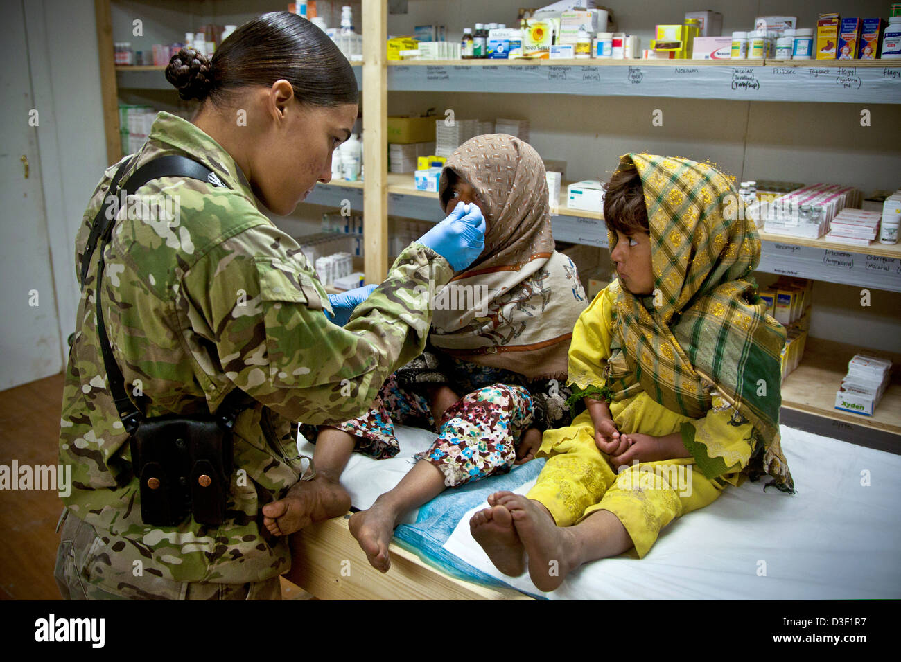 An Afghan girl watches as a US Marine gives her sister cough suppressant during a bi-weekly clinic for women and - Stock Image