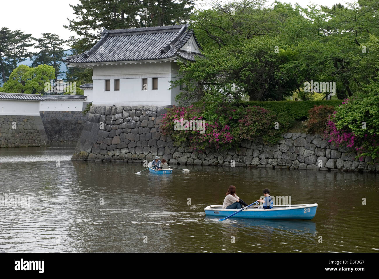 Boaters spend a relaxing afternoon navigating historic Odawara Castle moat past a guard tower and fortress walls - Stock Image
