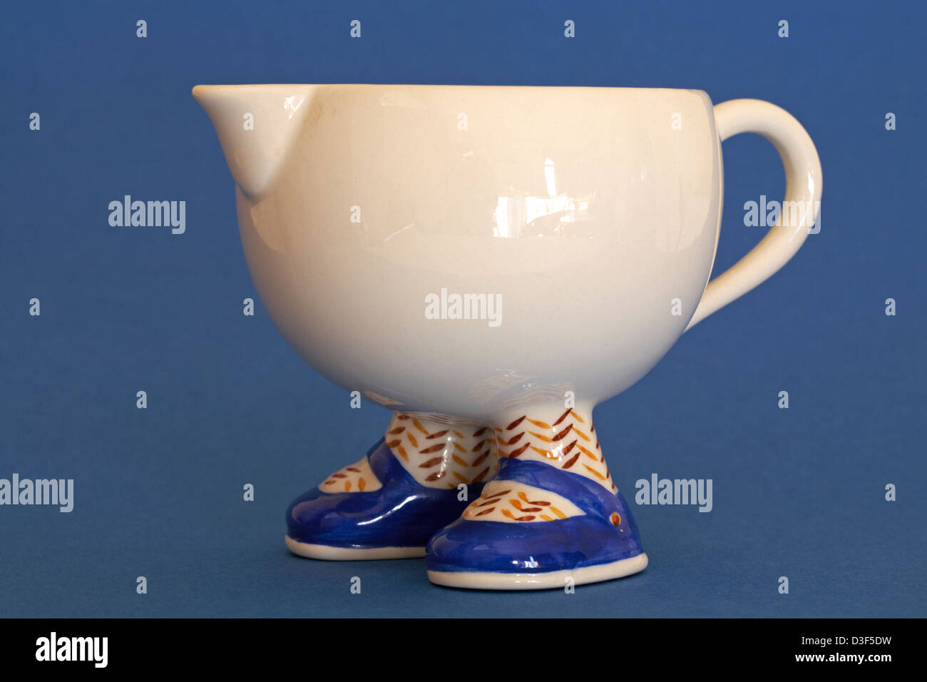 cream coloured jug with feet and shoes isolated on blue background Stock Photo
