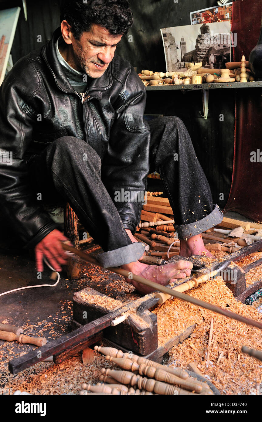 Man n a Medina  souk ,Marrakesh,  uses his feet  to operate his lathe to make decorative spindles for tourists - Stock Image