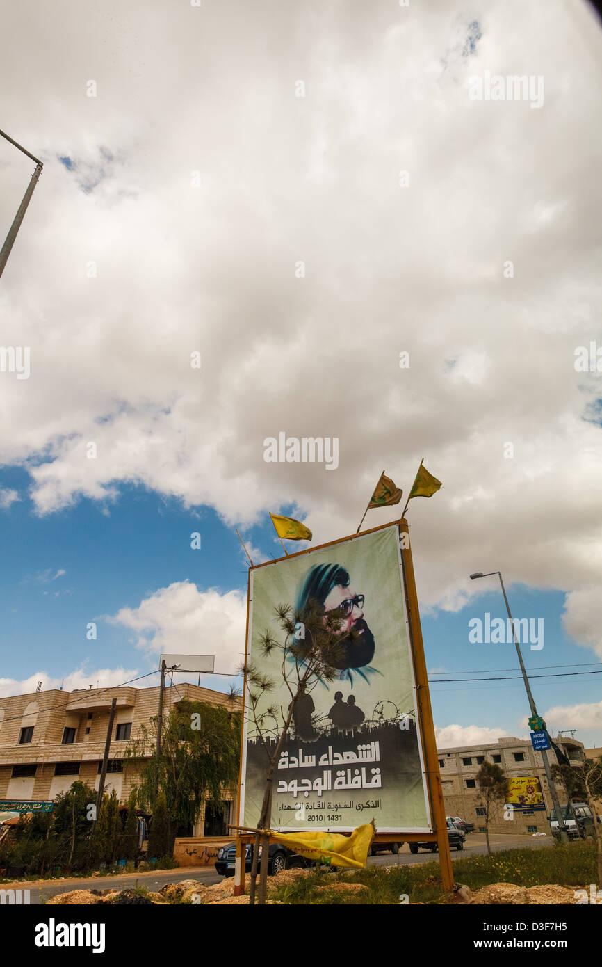 Billboards of Hassan Nasrallah under Hezbollah flags by highway in the Beqaa Valley, Lebanon. - Stock Image