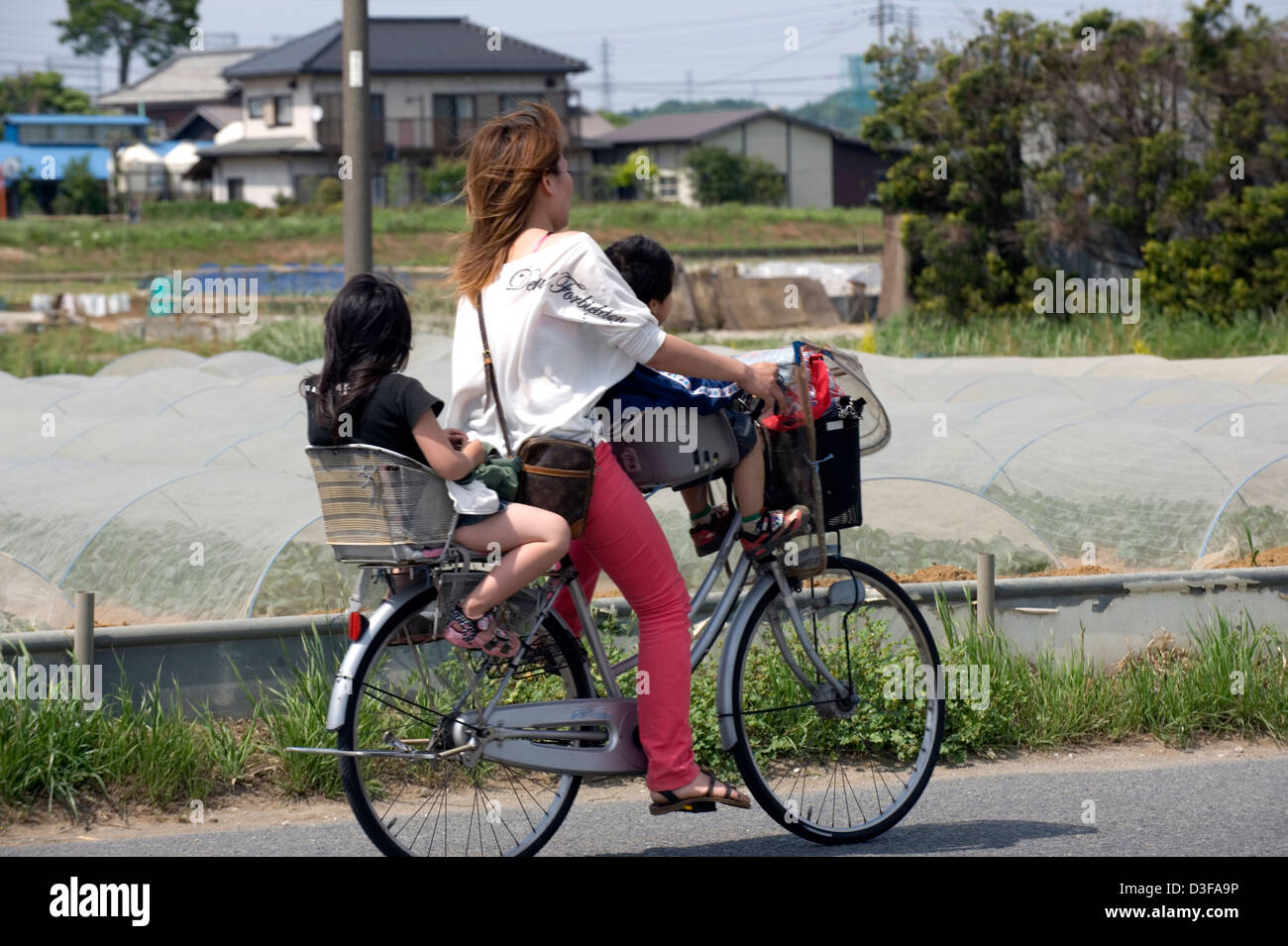 Mother rides through Kanagawa Prefecture countryside on a bicycle with son and daughter aboard in special seats - Stock Image