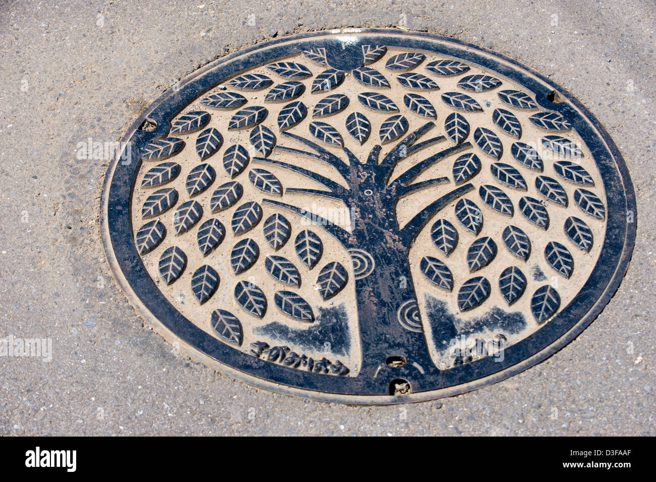 Artistic manhole cover in the town of Sagami, Kanagawa Prefecture shows a tree with leaves. - Stock Image