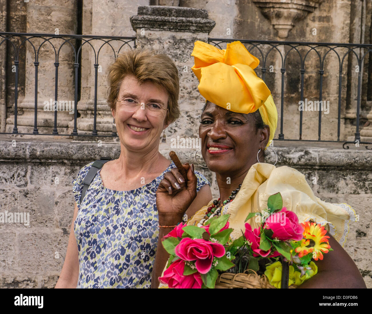 A Cuban cigar smoking dark skinned woman poses with a light skinned American tourist in Havana, Cuba. - Stock Image