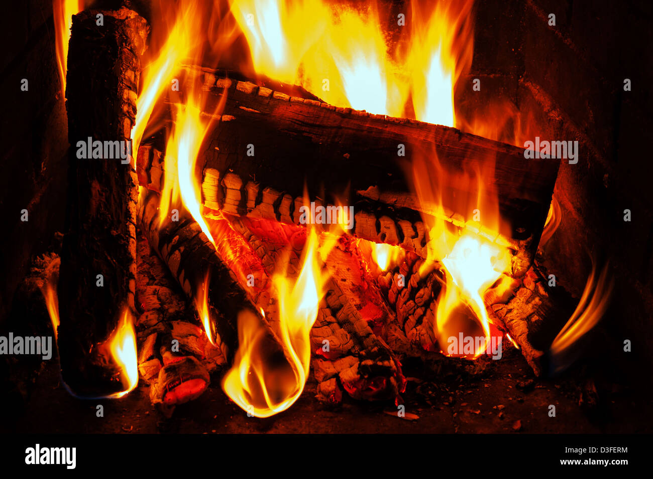 fireplace with oak firewood and flame - Stock Image