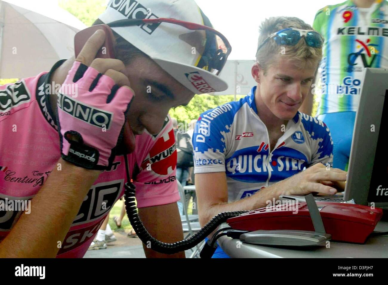 (dpa) - Spanish cyclist Isidor Nozal (L) (Team Once-Eroski) makes a quick  telephone call while Australian Michael Rogers (R) (Quick Step-Davitamon)  surfs ... 157a26da7