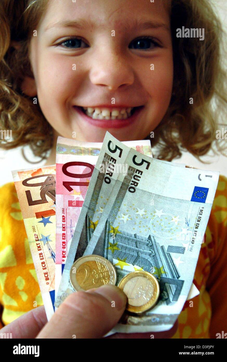 (dpa) - A symbolic picture shows a young girl smiling as she is handed over 73 euros, Hamburg, Germany, 9 July 2003. - Stock Image
