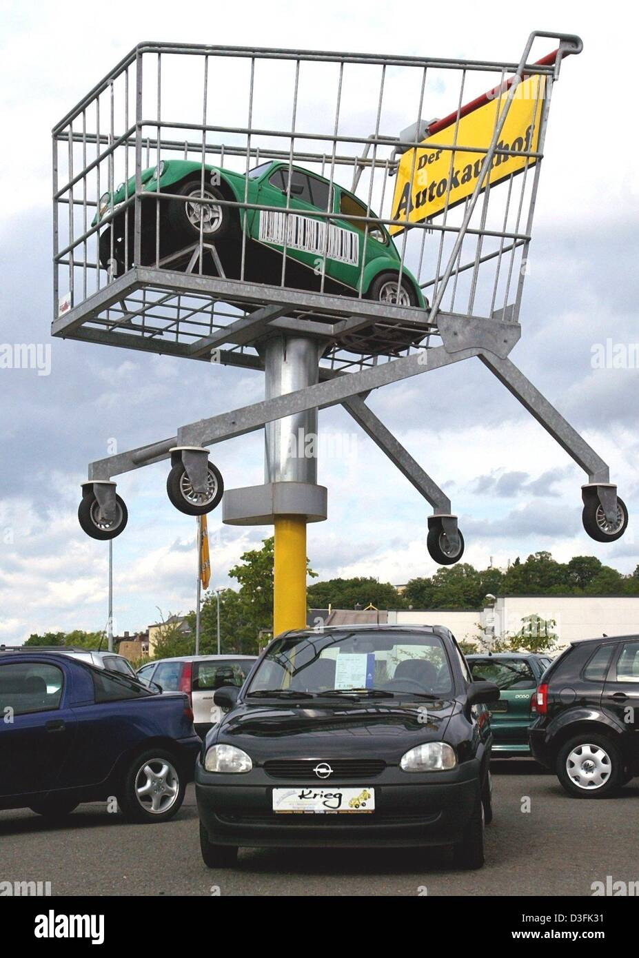 (dpa) - A VW beatle stands in an oversized shopping trolley as an eye-catcher towering above the sales car-park Stock Photo