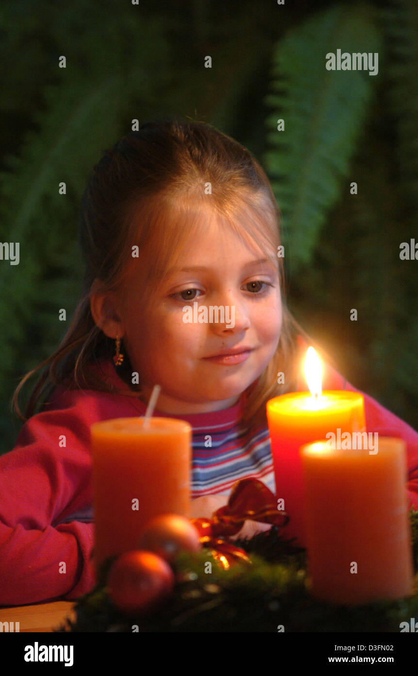 (dpa) - The little Lea looks dreamily into the flame of a candle on an advent wreath, in Germany, 25 November 2004. - Stock Image