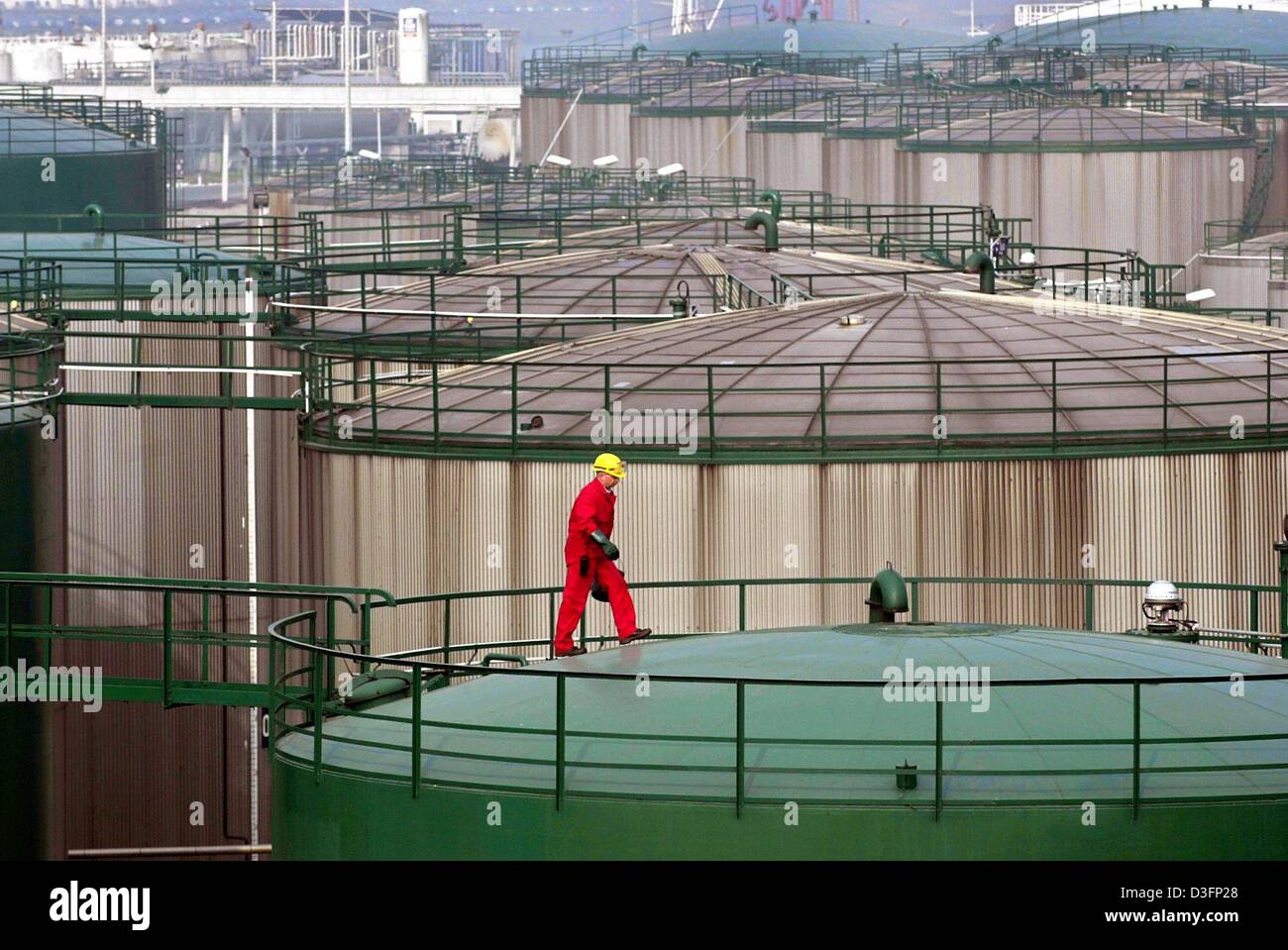 (dpa) - A worker walks across a giant oil tanks filled with petrol and crude oil  in a section of the harbour in - Stock Image