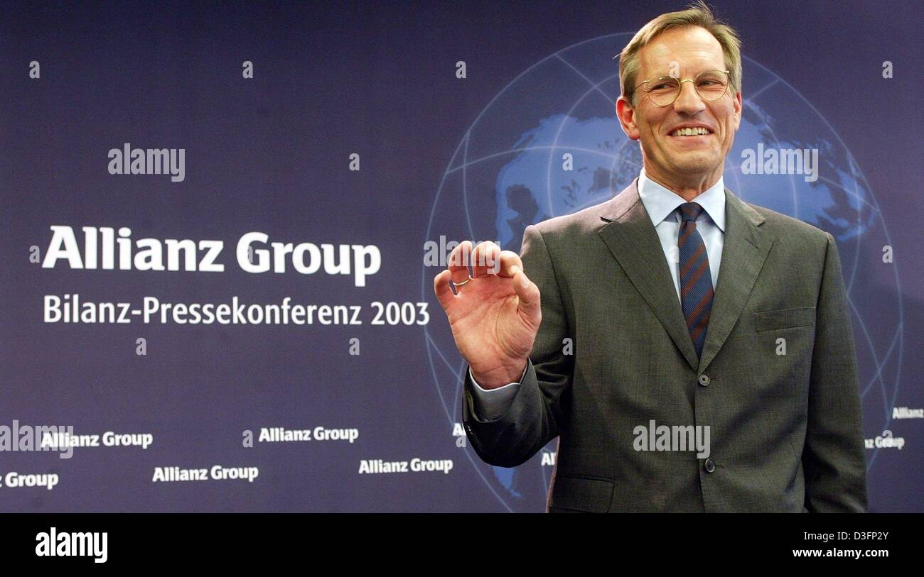 (dpa) - Michael Diekmann, new CEO of the Allianz AG, the financial services and insurance provider, stands in front of the company logo and smiles during a press conference in Munich, Germany, 20 March 2003. Diekmann continues the company policy of providing integrated financial services by holding on to the lossy Dresdner Bank. The Allianz AG wants to raise new capital in billions Stock Photo
