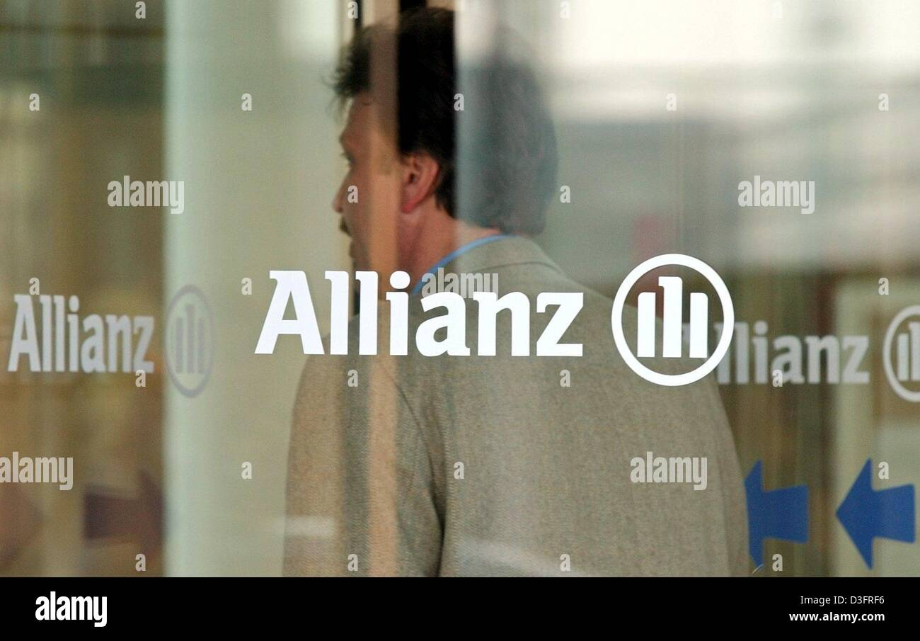 (dpa) - An employee of Allianz AG, the financial services and insurance provider, stands behind a glass revolving door with the company logo on it at the company's headquarters in Munich, Germany 20 March 2003. Michael Diekmann, new CEO of the Allianz AG, said during a press conference that the company should continue its policy of providing integrated financial services by holding Stock Photo
