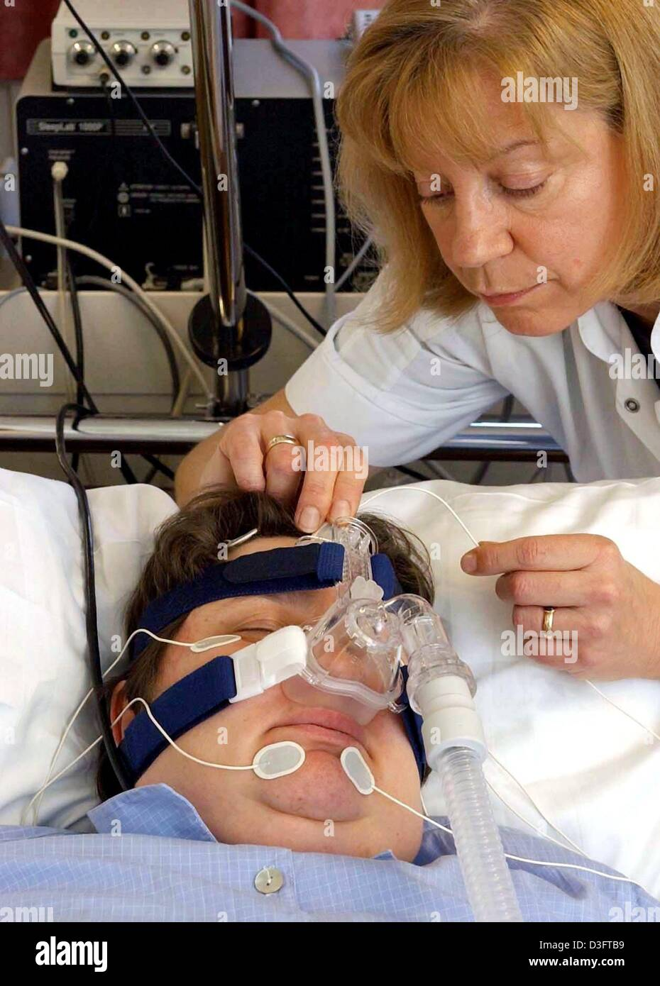 (dpa) - Medical Assistant Julia Witte is checking the electrodes and the silicone snoring mask on a patient, University - Stock Image