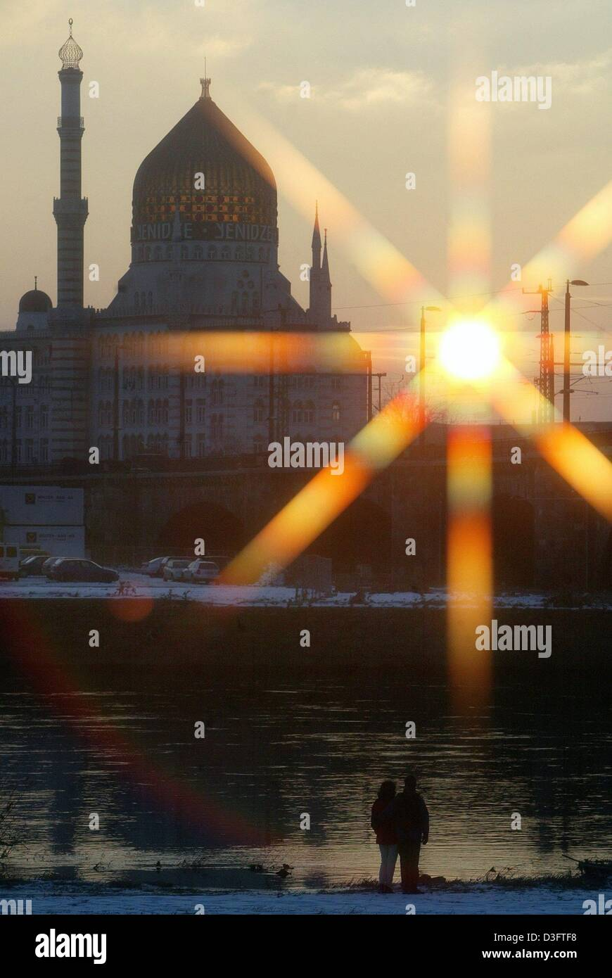 (dpa) - A couple standing on the banks of the Elbe River gazes upon the sunset over the mosque-like Yenidze building - Stock Image