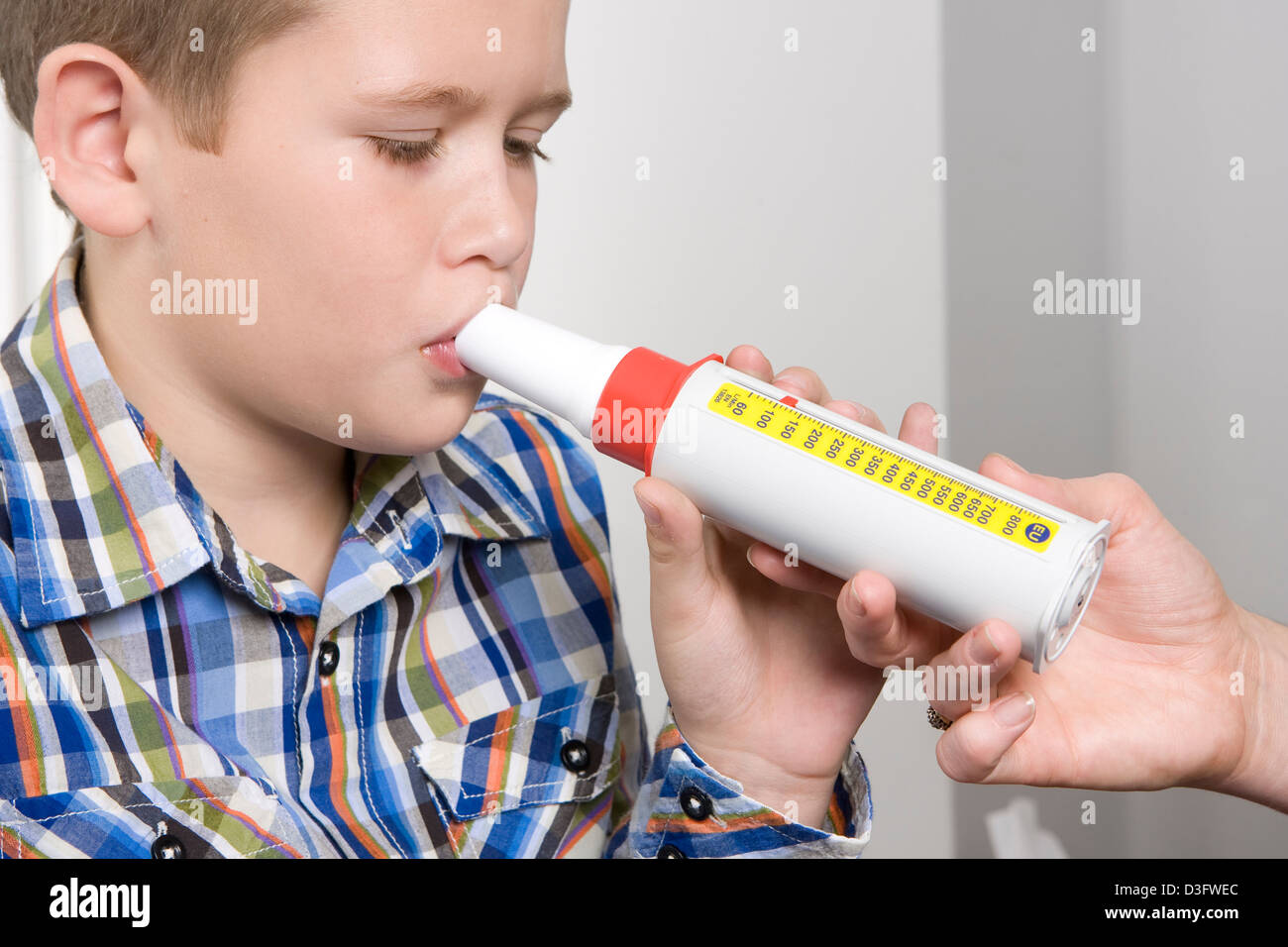 A young female nurse administering a peak flow meter to a young male child patient at a Doctor's Surgery. - Stock Image