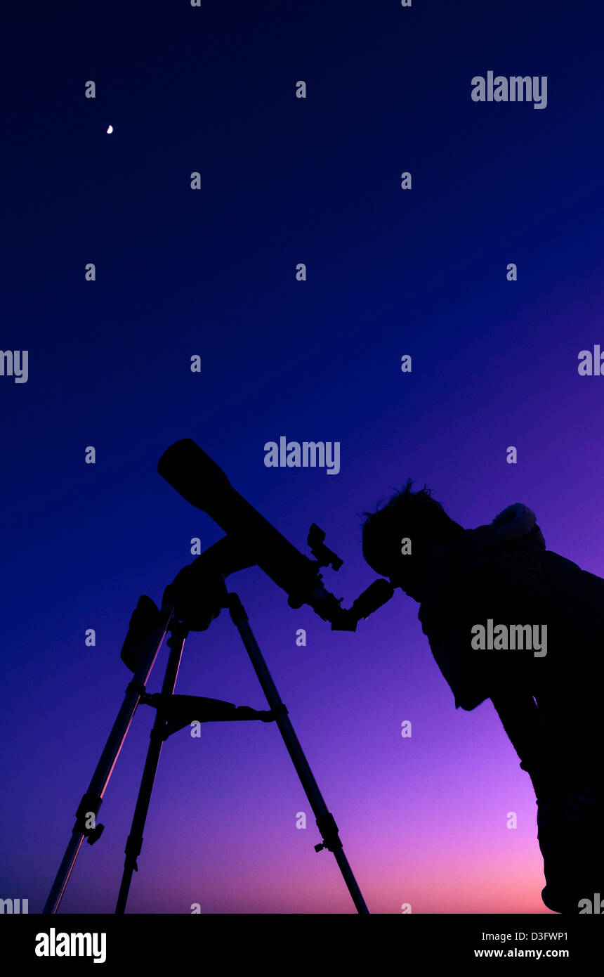 The silhouette of a teenage girl stargazing with a telescope at dusk with the moon overhead. - Stock Image