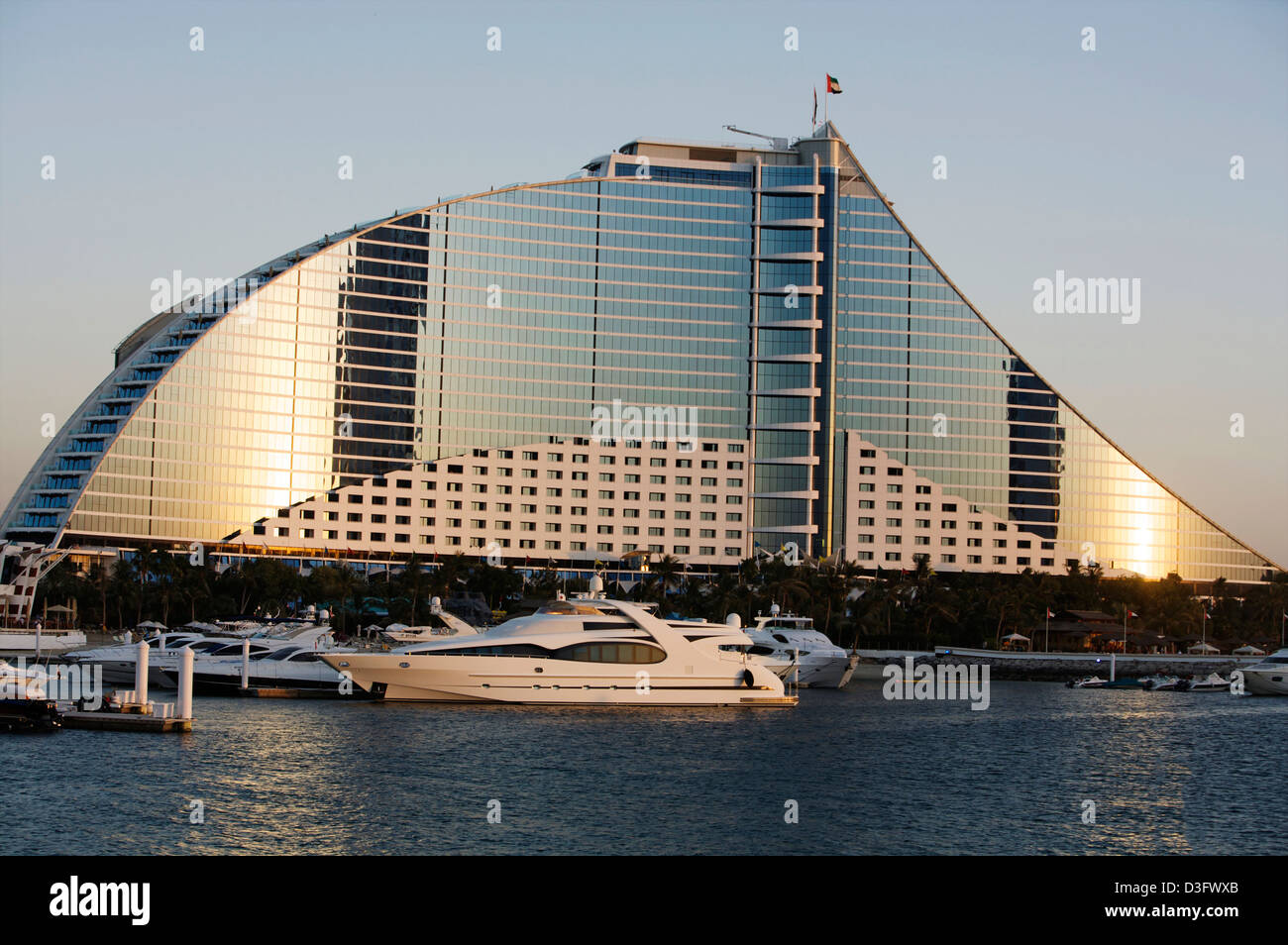 Jumeirah Beach Hotel Dubai with a luxury yacht in the foreground at sunset - Stock Image